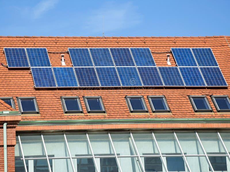 Los paneles solares en el tejado de la construcción de escuelas imagenes de archivo