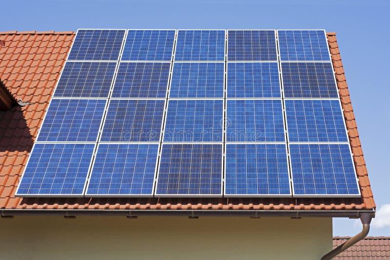 Los paneles solares en el tejado rojo de la casa Fondo de energía solar fotografía de archivo