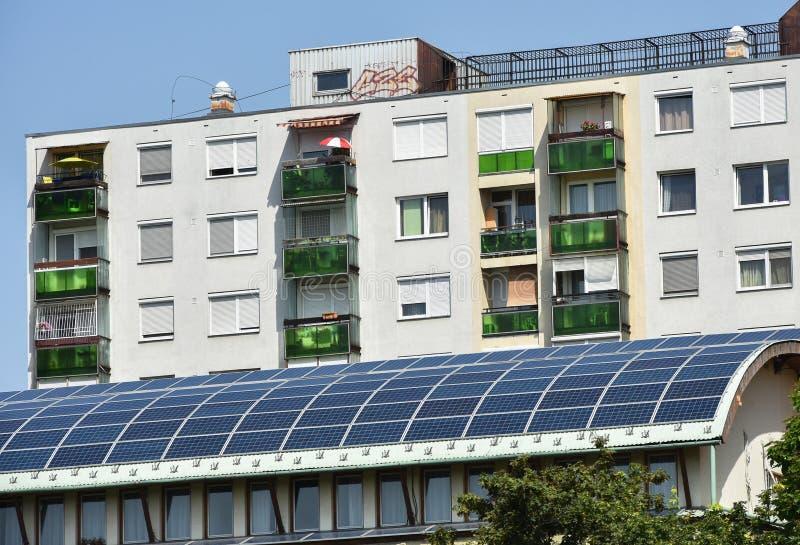 Los paneles solares en el tejado y una construcción de viviendas fotografía de archivo libre de regalías