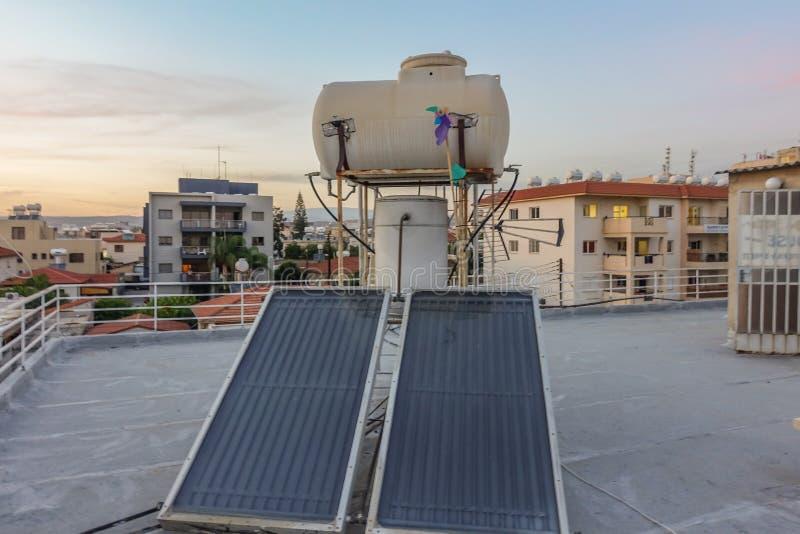 Los paneles solares y los tanques de agua en un tejado foto de archivo