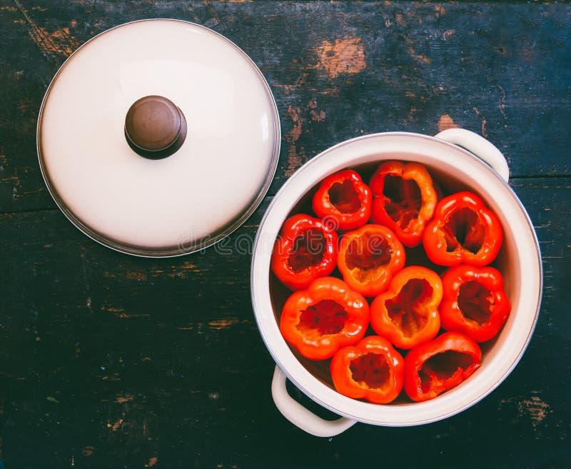 Los paprikas rojos pelados de las semillas se prepararon para rellenar en un cazo fotografía de archivo