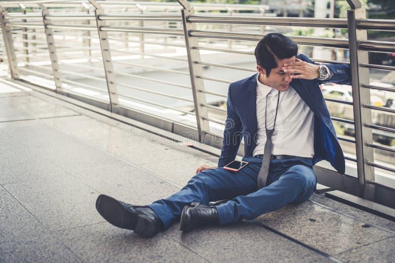 Los parados del hombre de negocios de la compañía que se sienta en la calle y su cabeza abrochada mano, él es sensación de subray imagen de archivo