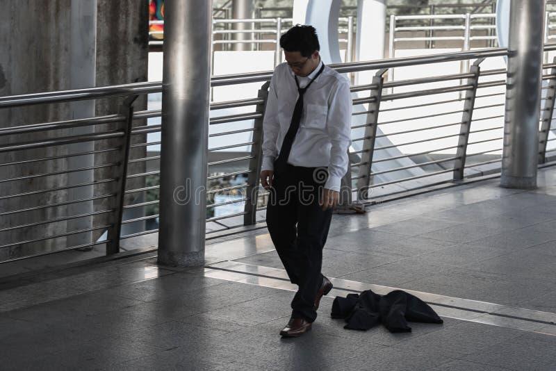 Los parados subrayaron al hombre de negocios asiático joven que se sentaba en piso al aire libre Concepto del fracaso y del despi imágenes de archivo libres de regalías