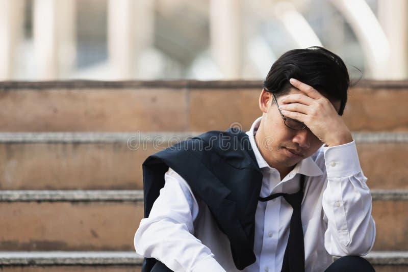 Los parados subrayaron al hombre de negocios asiático joven que sufría de la depresión severa Concepto del fracaso y del despido imagenes de archivo