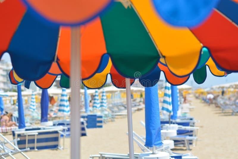 Los paraguas coloridos les gusta el arco iris en la playa fotos de archivo