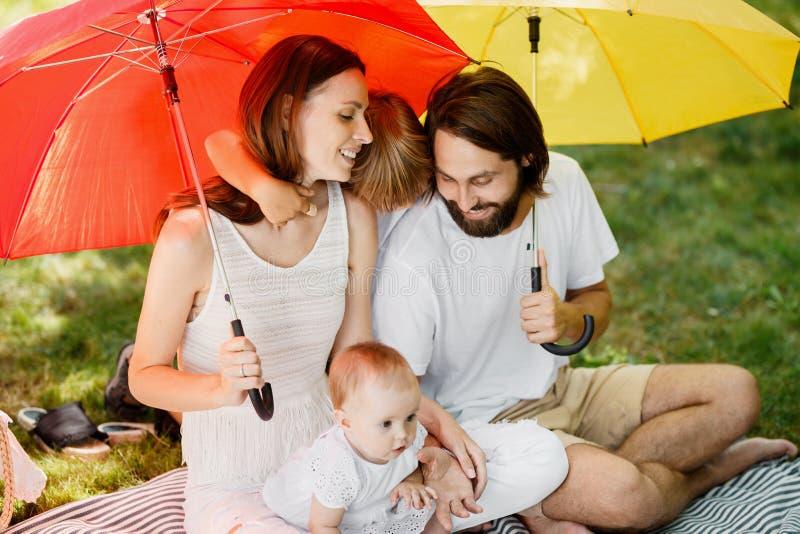 Los paraguas grandes brillantes cubren a la familia feliz vestida en la ropa blanca que se sienta en la manta del sol foto de archivo