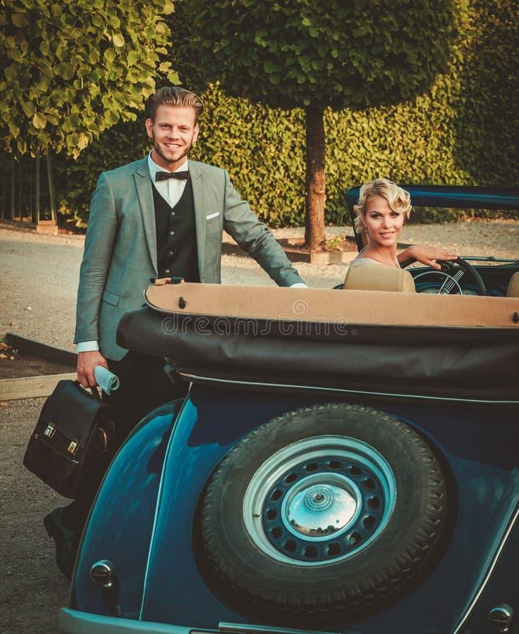 Los pares acercan al coche clásico fotografía de archivo libre de regalías
