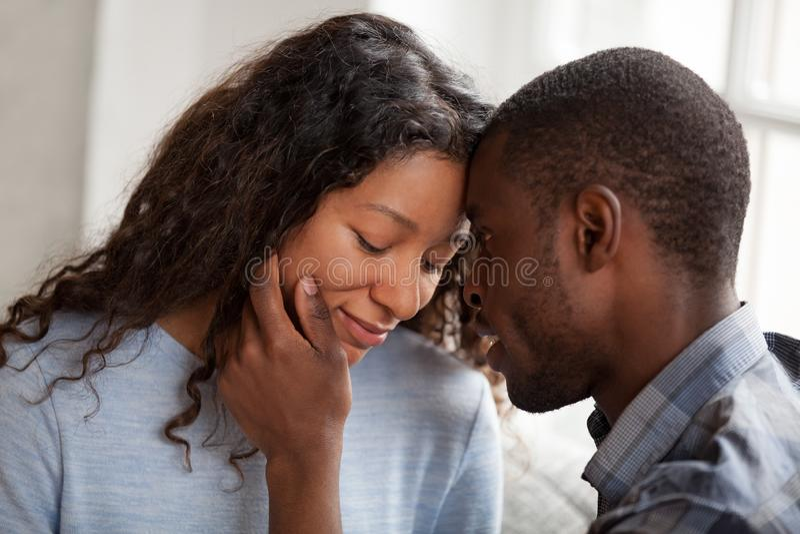 Los pares africanos en amor tienen una fecha en casa fotografía de archivo libre de regalías