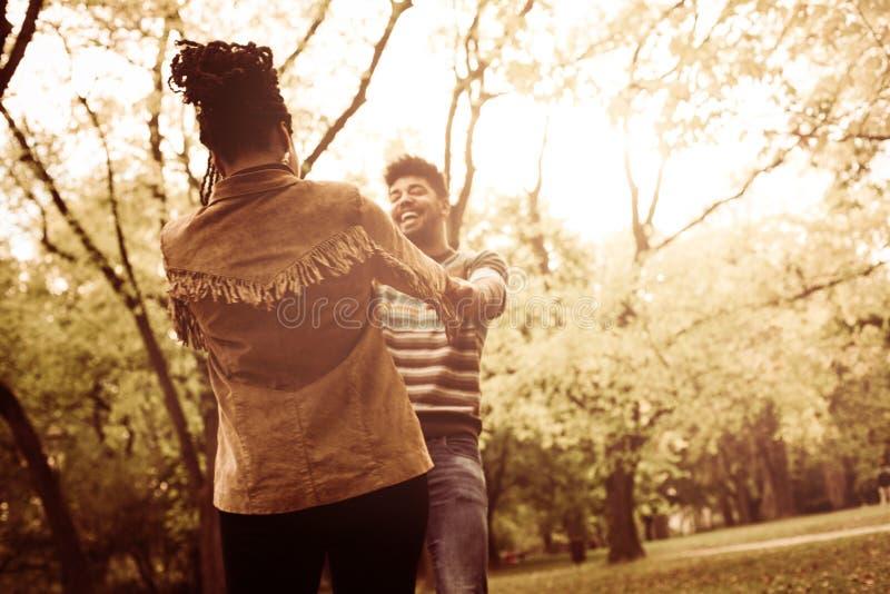 Los pares afroamericanos en el parque que lleva a cabo las manos y giran i foto de archivo
