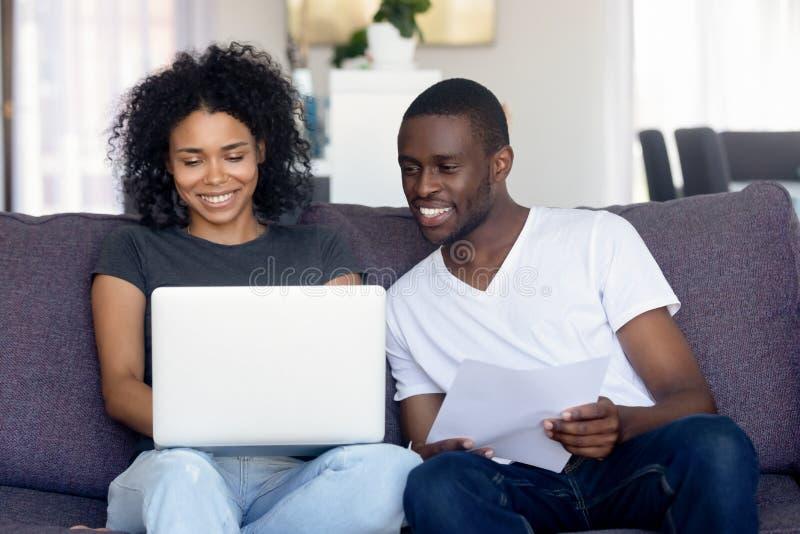 Los pares afroamericanos felices usando el ordenador portátil, reciben buenas noticias foto de archivo