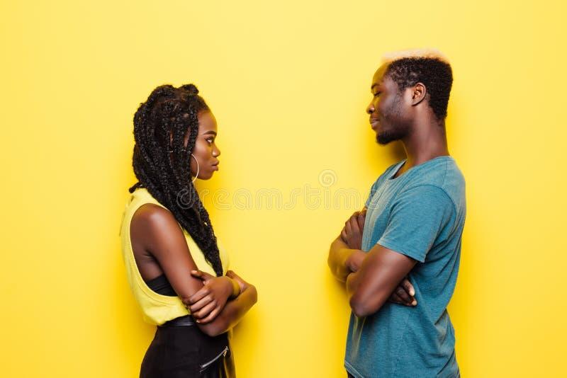 Los pares afroamericanos jovenes ofendieron a cara a cara derecho aislados en fondo amarillo fotografía de archivo libre de regalías