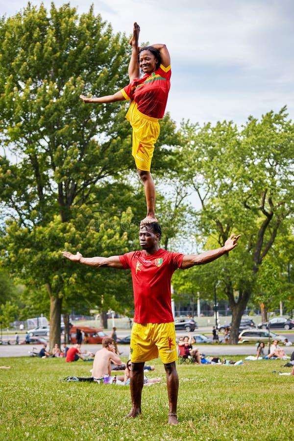 Los pares afroamericanos que realizan la acrobacia muestran delante de la audiencia en parque real del soporte fotografía de archivo