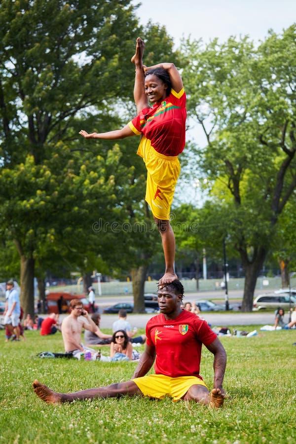 Los pares afroamericanos que realizan la acrobacia muestran delante de la audiencia en parque real del soporte imagen de archivo libre de regalías