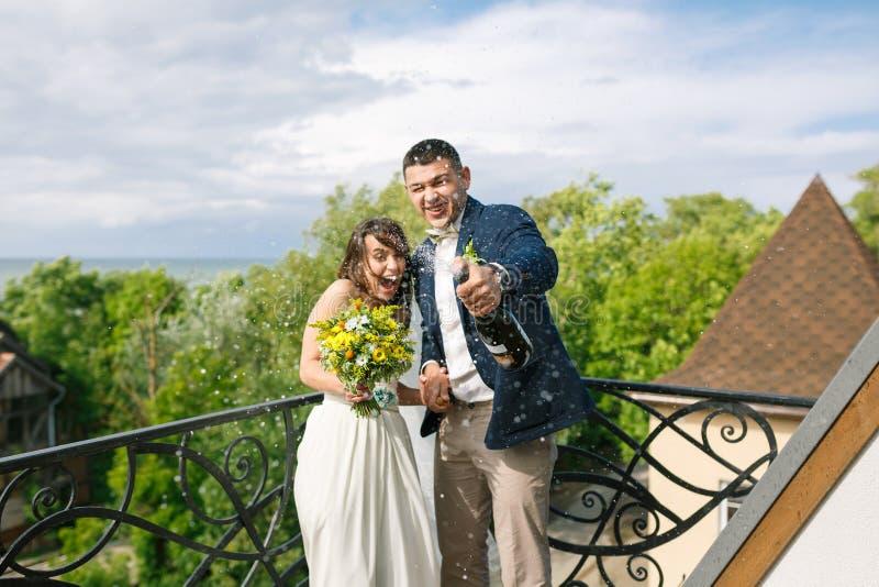Los pares alegres abren el champán foto de archivo