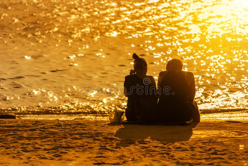 Los pares aman sentar la relajación en la playa tropical durante tiempo de la puesta del sol imagenes de archivo