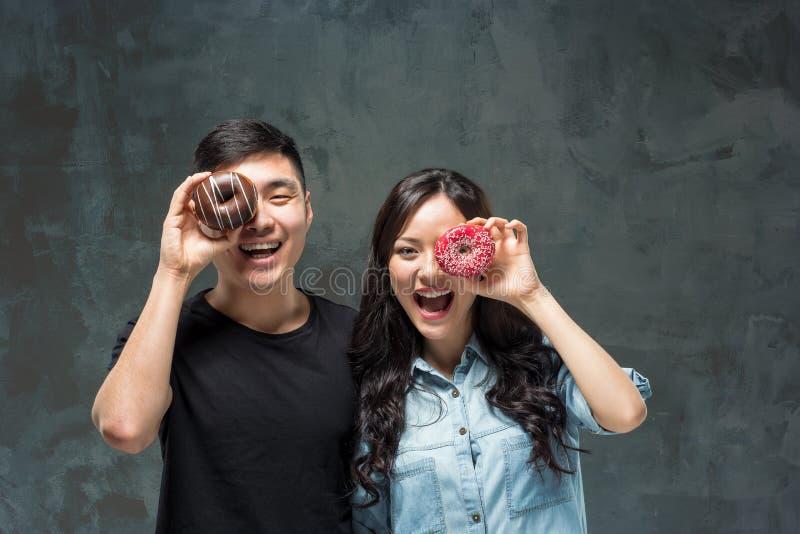 Los pares asiáticos jovenes disfrutan de consumición del buñuelo colorido dulce imagen de archivo libre de regalías