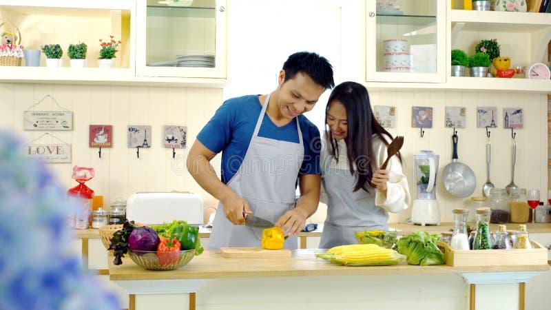 Los pares asiáticos jovenes gozan a preparar la comida en la cocina imagen de archivo libre de regalías