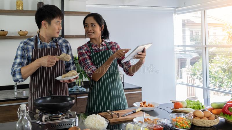 Los pares asiáticos jovenes son felices de cocinar juntos, dos familias se están ayudando a prepararse para cocinar en la cocina imagen de archivo libre de regalías