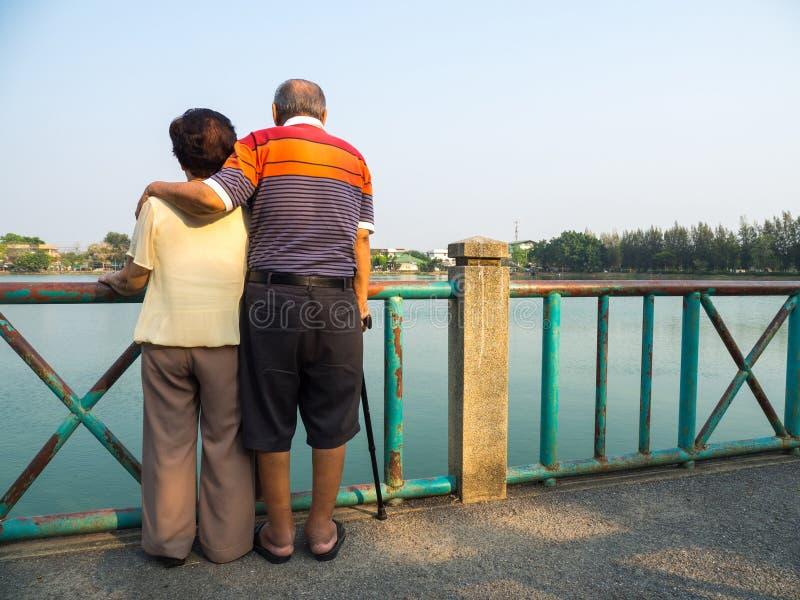 Los pares asiáticos mayores románticos felices se colocan en el puente delante del lago El marido se coloca con su esposa Concept foto de archivo