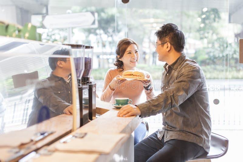 Los pares asiáticos se relajan en café imagen de archivo libre de regalías