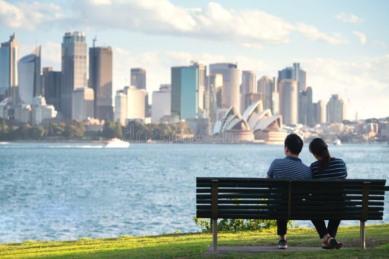 Los pares asiáticos se sientan y se relajan después de correr en un parque en Sydney fotos de archivo libres de regalías