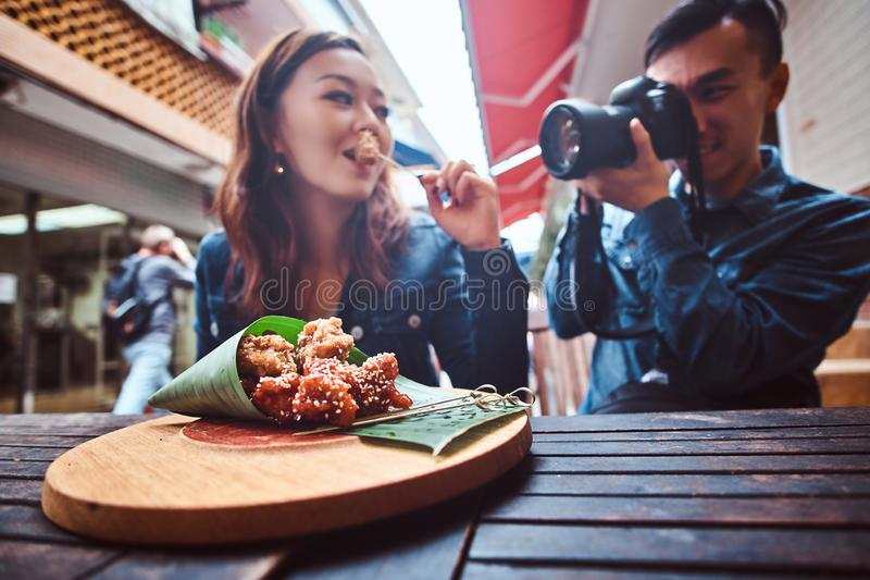 Los pares asi?ticos jovenes disfrutan del tiroteo chino de la comida y de foto foto de archivo