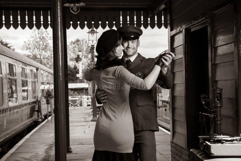 Los pares atractivos bailan en la plataforma del ferrocarril con el tocadiscos portátil fotos de archivo libres de regalías