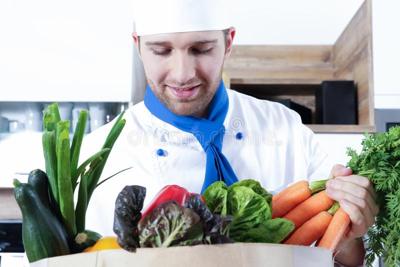 Los pares atractivos hermosos del hombre de la mujer como cocinero están cocinando en una cocina foto de archivo