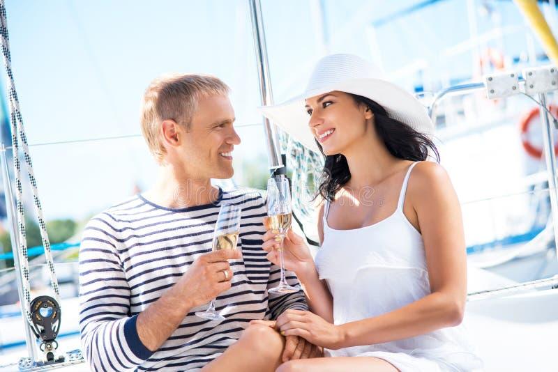 Los pares atractivos y ricos tienen un partido en un barco imagen de archivo libre de regalías