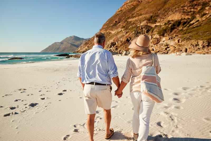 Los pares blancos mayores que caminan en una playa que lleva a cabo las manos, detrás visión, longitud del tres cuartos, se cierr fotografía de archivo