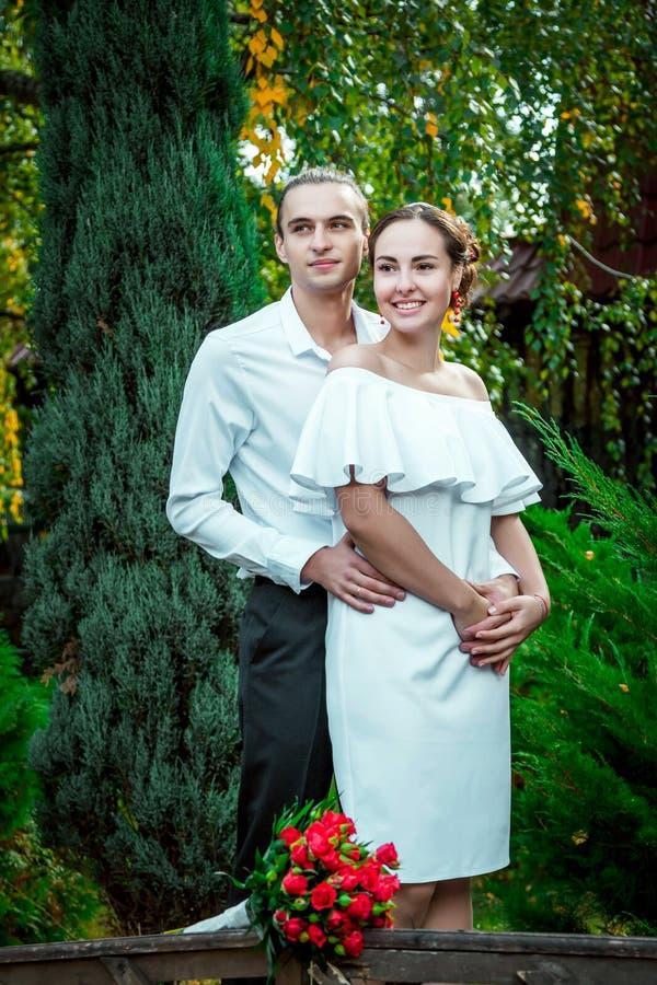 Los pares cariñosos felices de la boda que abrazan en el otoño parquean foto de archivo libre de regalías
