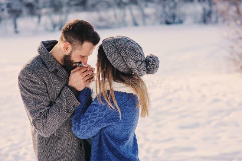 Los pares cariñosos felices que caminan en el bosque nevoso del invierno, pasando la Navidad vacation juntos Actividades estacion imagen de archivo libre de regalías