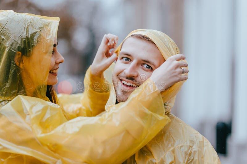 Los pares cariñosos románticos, el individuo y su novia vestidos en impermeables amarillos están abrazando en la calle bajo la fotos de archivo