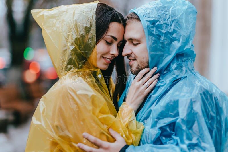 Los pares cari?osos rom?nticos, el individuo y su novia en los impermeables se colocan cara a cara en la calle bajo la lluvia imágenes de archivo libres de regalías