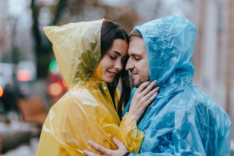 Los pares cari?osos rom?nticos, el individuo y su novia en los impermeables se colocan cara a cara en la calle bajo la lluvia imagenes de archivo