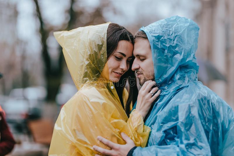 Los pares cari?osos rom?nticos, el individuo y su novia en los impermeables se colocan cara a cara en la calle bajo la lluvia imagen de archivo