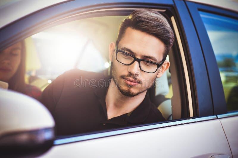 Los pares caucásicos jovenes en el coche que se divierte en viaje por carretera y utilizan un smartphone fotos de archivo libres de regalías