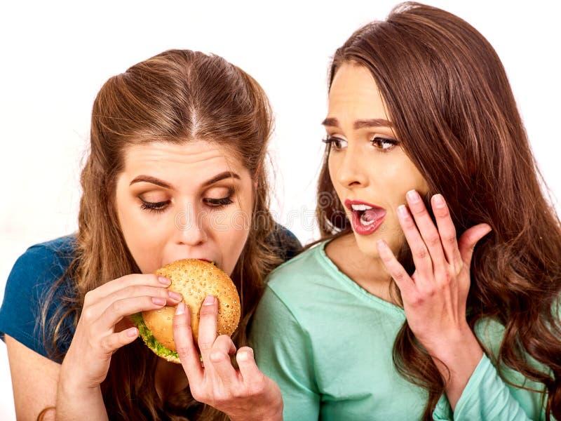 Los pares comen la hamburguesa Los amigos toman los alimentos de preparación rápida imágenes de archivo libres de regalías