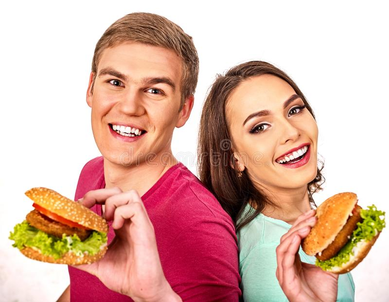 Los pares comen la hamburguesa Las mujeres y el hombre toman los alimentos de preparación rápida fotografía de archivo