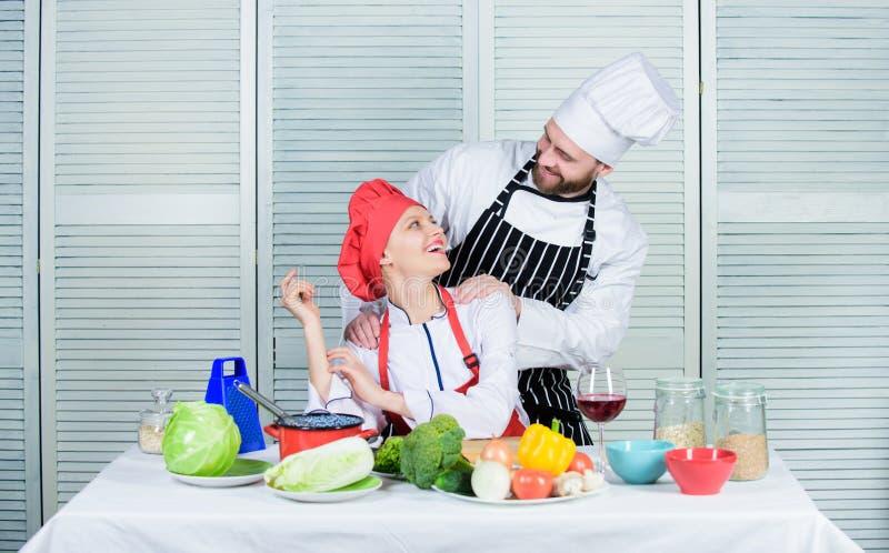 Los pares compiten en artes culinarios Razones por las que pares que cocinan junto El cocinar con su cónyuge puede fortalecer foto de archivo libre de regalías