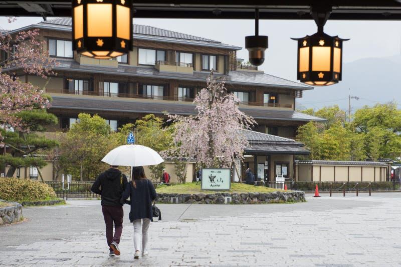 Los pares con el paraguas salen del ferrocarril de Arashiyama foto de archivo libre de regalías