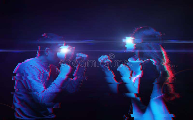 Los pares con las auriculares de la realidad virtual están jugando el juego y luchar Imagen con efecto de la interferencia foto de archivo