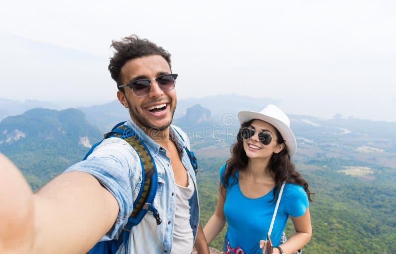 Los pares con las mochilas toman la foto de Selfie sobre el senderismo del paisaje de la montaña, el hombre joven y la mujer en t fotos de archivo libres de regalías