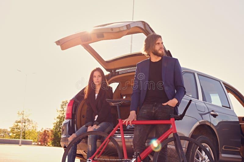 Los pares con sola velocidad montan en bicicleta cerca del coche con el tronco abierto imagen de archivo