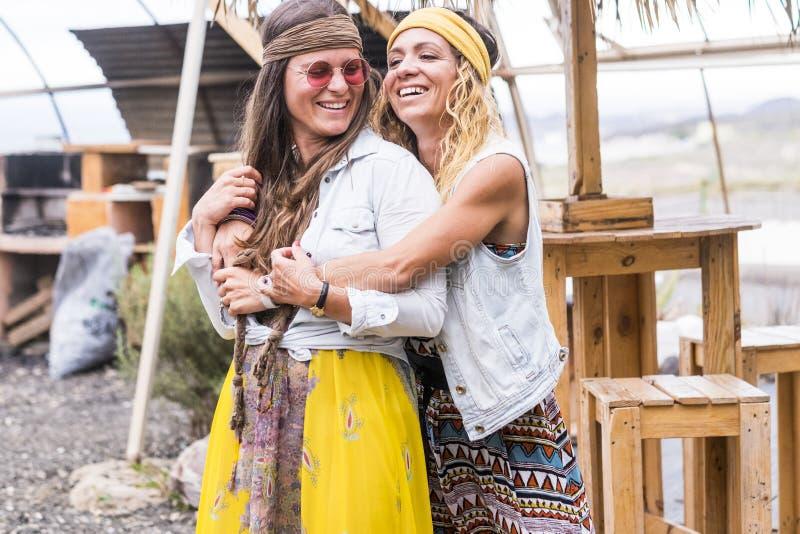 Los pares de los amigos locos de las hembras se divierten y gozan de la ropa y de los accesorios retros viejos del estilo del hip fotografía de archivo libre de regalías
