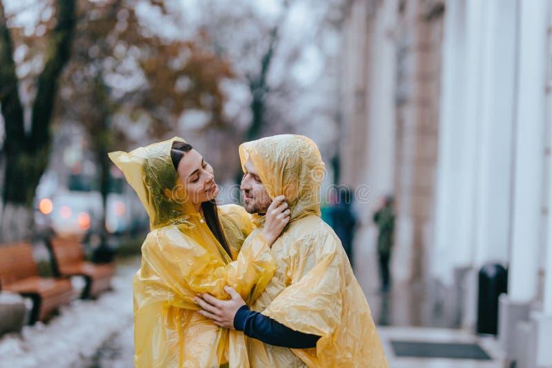 Los pares de amor, el individuo y su novia vestidos en impermeables amarillos están abrazando en la calle bajo la lluvia fotografía de archivo libre de regalías
