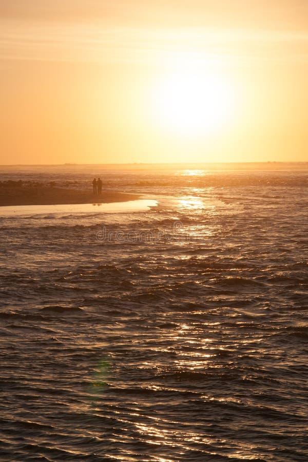 Los pares de amor están caminando en la playa del mar en los rayos calientes de la puesta del sol fotografía de archivo libre de regalías