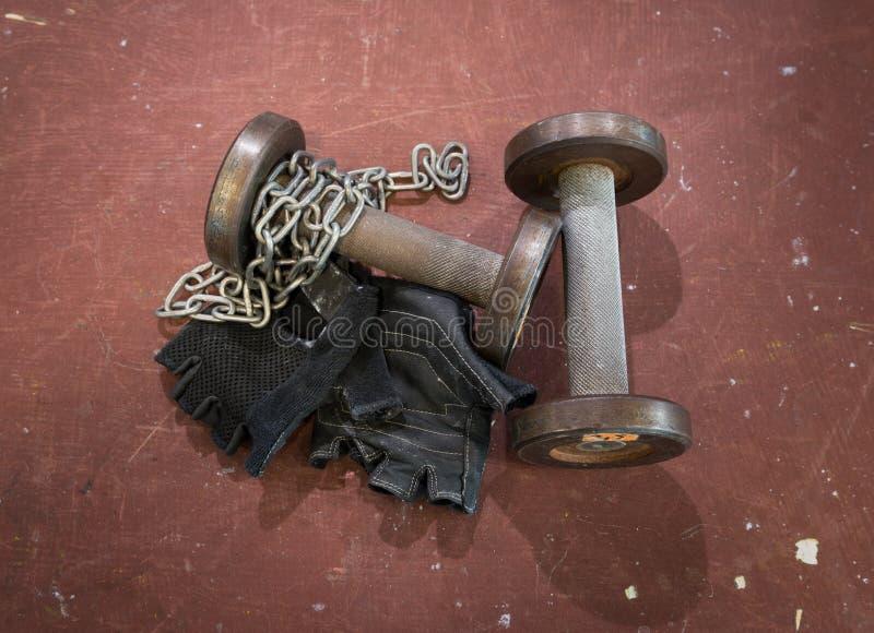 Los pares de aptitud ennegrecen guantes con la cadena de plata y dos utilizaron pequeñas pesas de gimnasia contra el fondo rojo,  foto de archivo