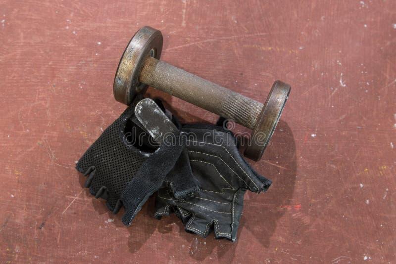 Los pares de aptitud ennegrecen guantes con pequeña pesa de gimnasia usada contra el fondo rojo, anaranjado, superficie Aptitud y imagenes de archivo