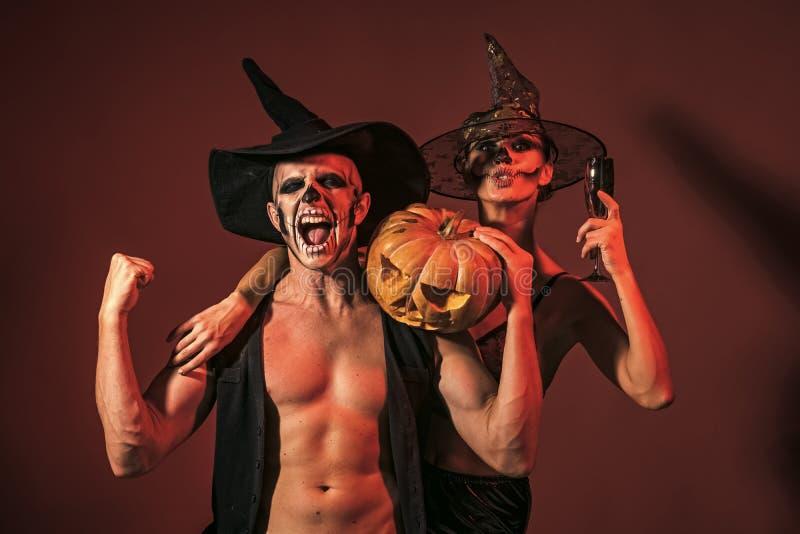 Los pares de Halloween con maquillaje en cara de grito sostienen la calabaza imagen de archivo libre de regalías